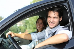 Couple cheerfully driving at the wheel