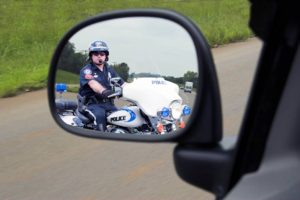 Police officer on motorcycle in rear mirror view